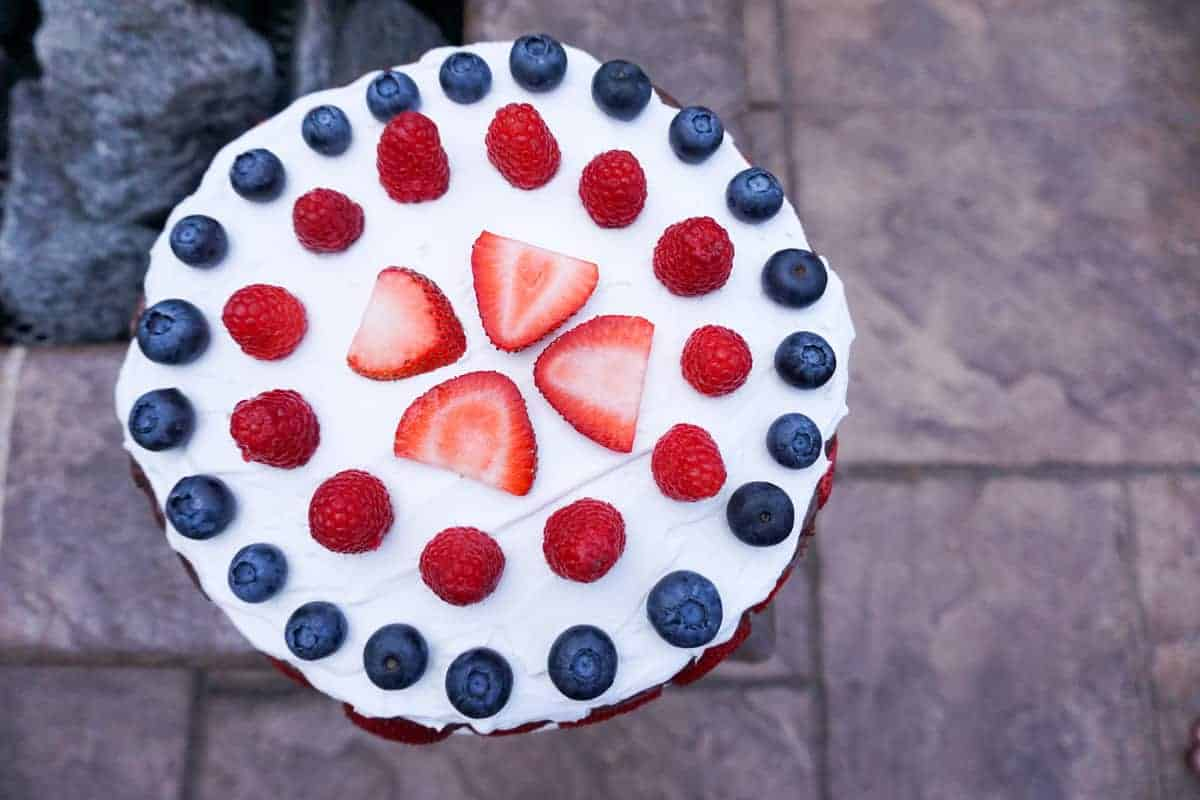strawberries, raspberries and blue berries aranged in concentric circles on coconut whip cream on a chocolate cake near a fire pit.