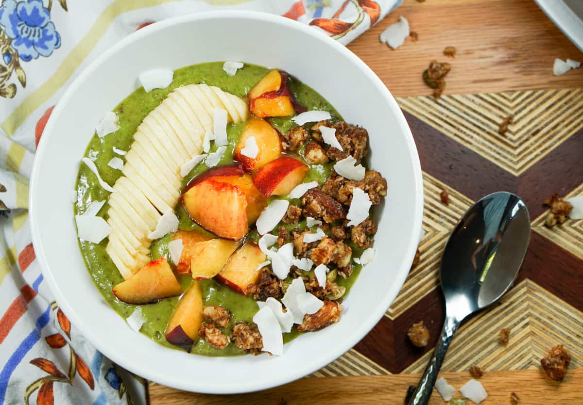 Peaches n Kale Smoothie Bowl Recipe - A delicious peaches n' cream smoothie bursting with antioxidants and protein. Topped with fruit and wholesome granola, it's a perfect way to start the day or treat yourself at night.