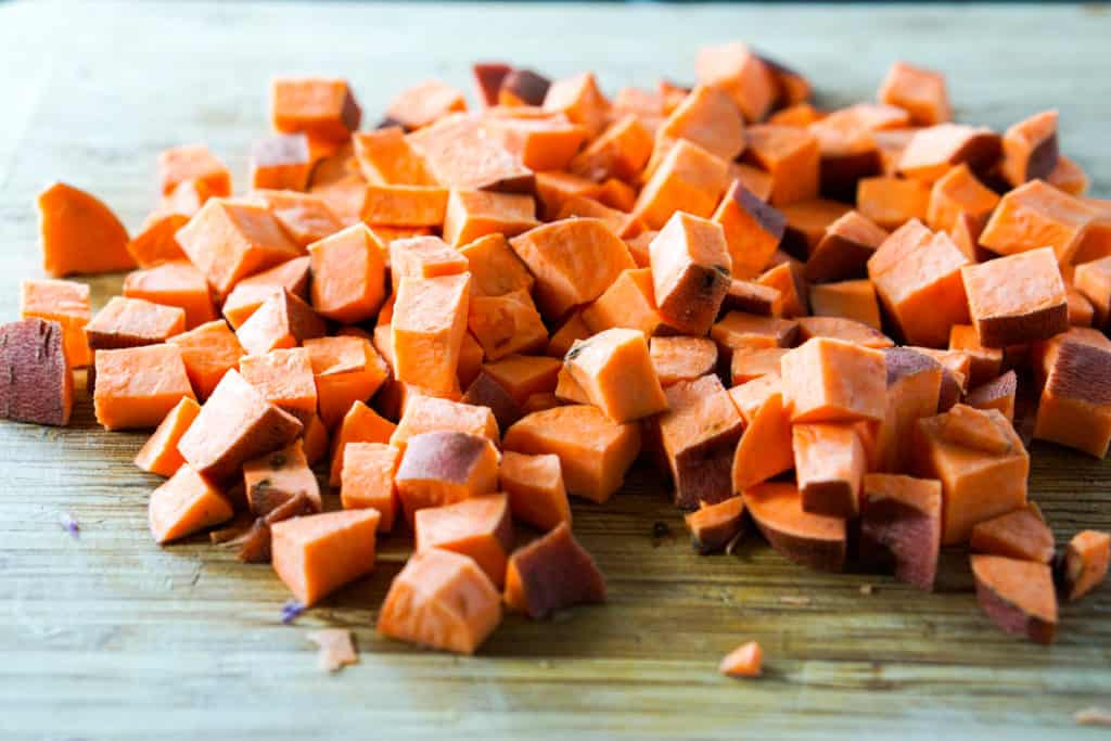 uniformly diced sweet potatoes on cutting board, skins on