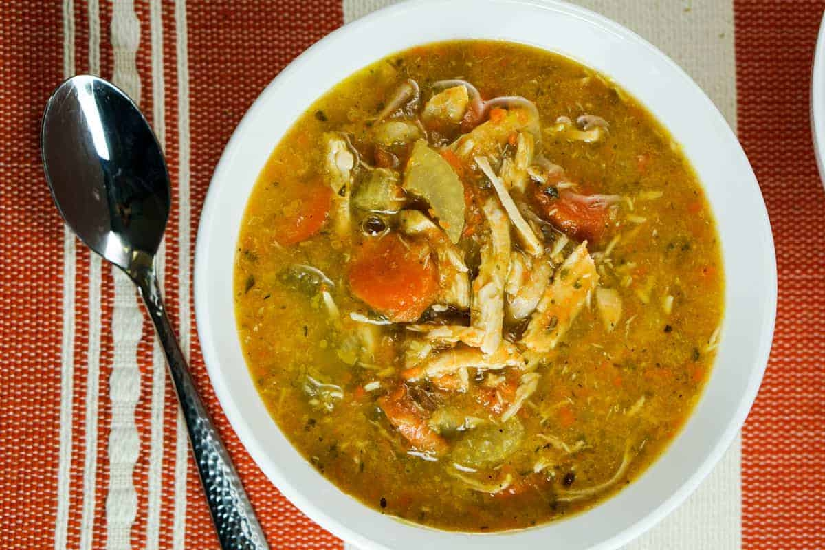 Bowl of chicken vegetables soup on burnt orange and white tablecloth and spoon