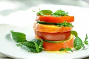 Peach Tomato Mint Salad Stack Recipe - Simply slice fresh peaches, tomatoes and cucumbers, stacking with mint to create this great appetizer, light meal or side salad. This will definitely be a recipe to impress your friends at your next barbq or family dinner!