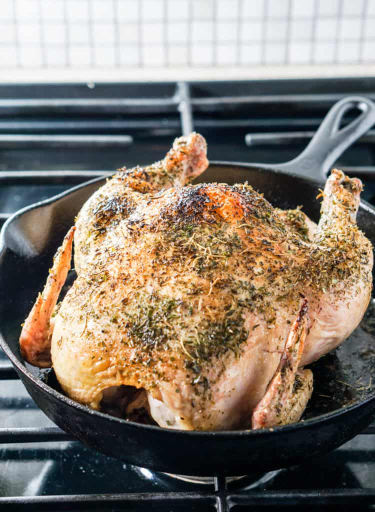 Herb coated roasted chicken in a cast iron skillet on a stove top