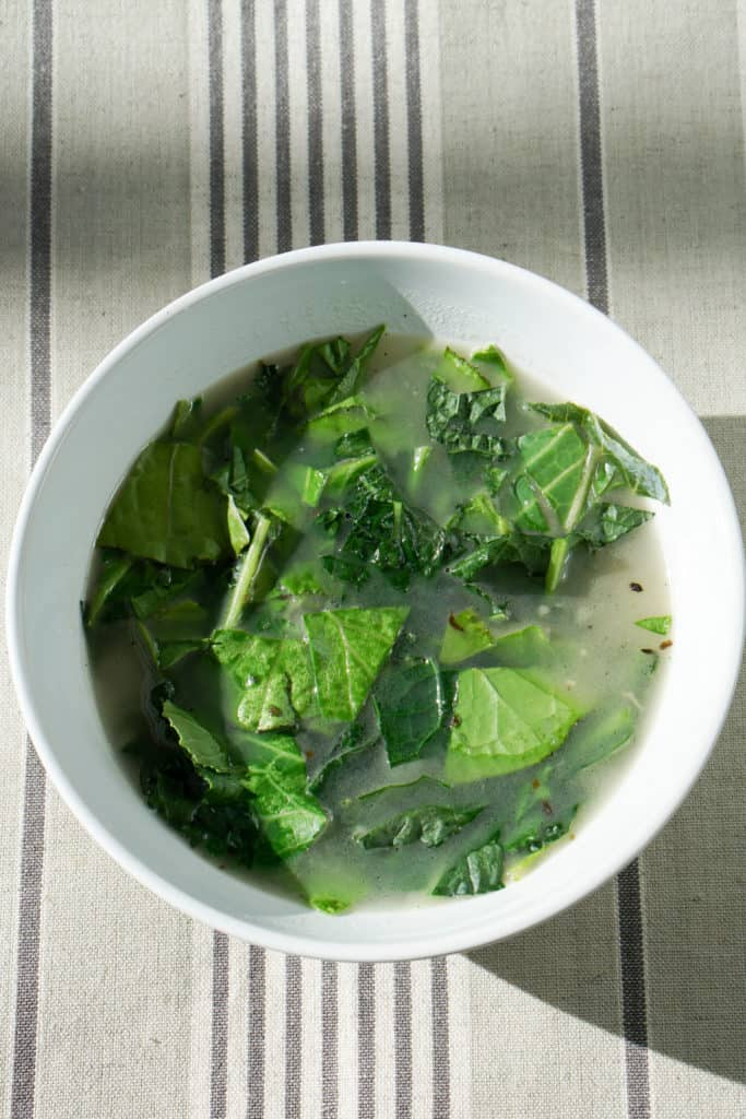 Try this nourishing bone broth over winter greens recipe is a quick and healthy meal that will reset your body after overindulging. Healthy + Delicious