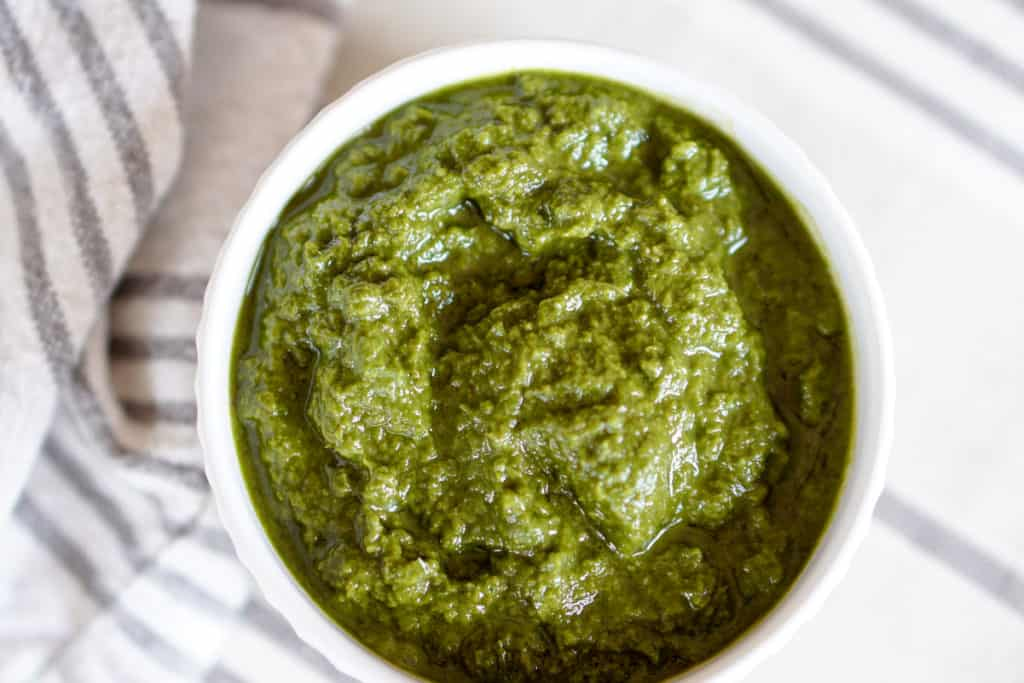 This Awesome Kale Green Sauce recipe is packed with delicious nutritious greens. 5 ingredients, 5 minutes. Use for a healthy kick on Pizza, Salads, + fries.