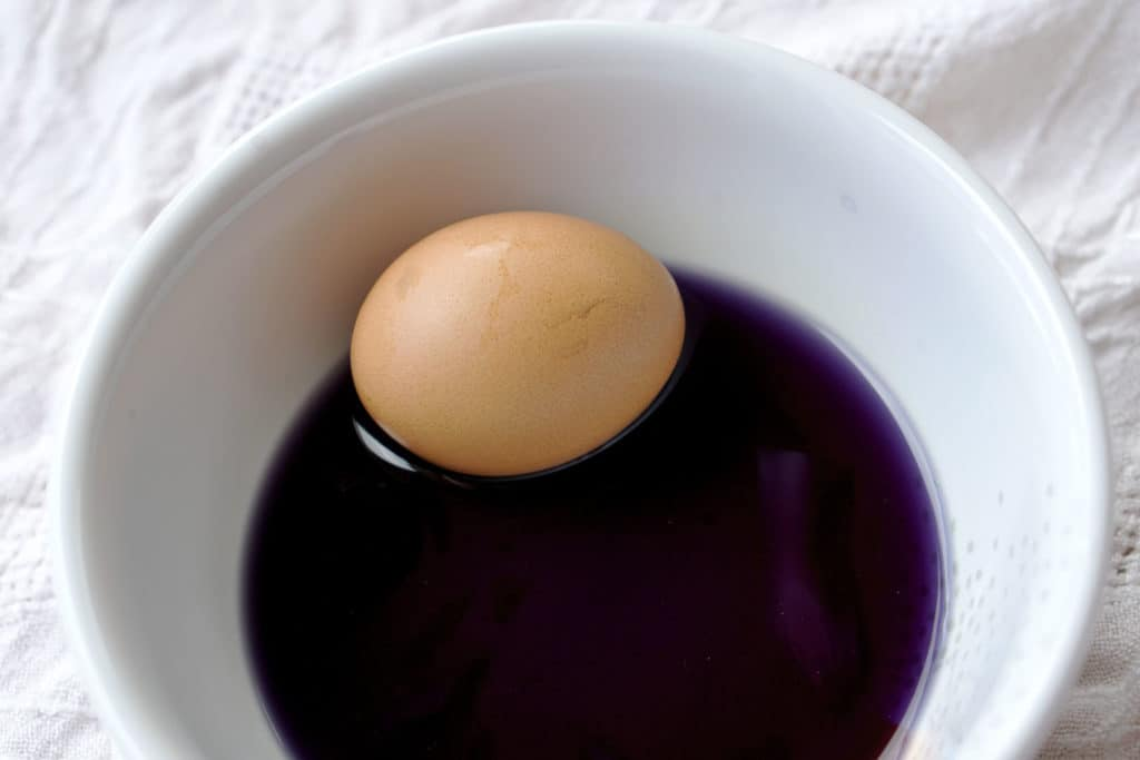 A brown egg in purple dye in a white bowl