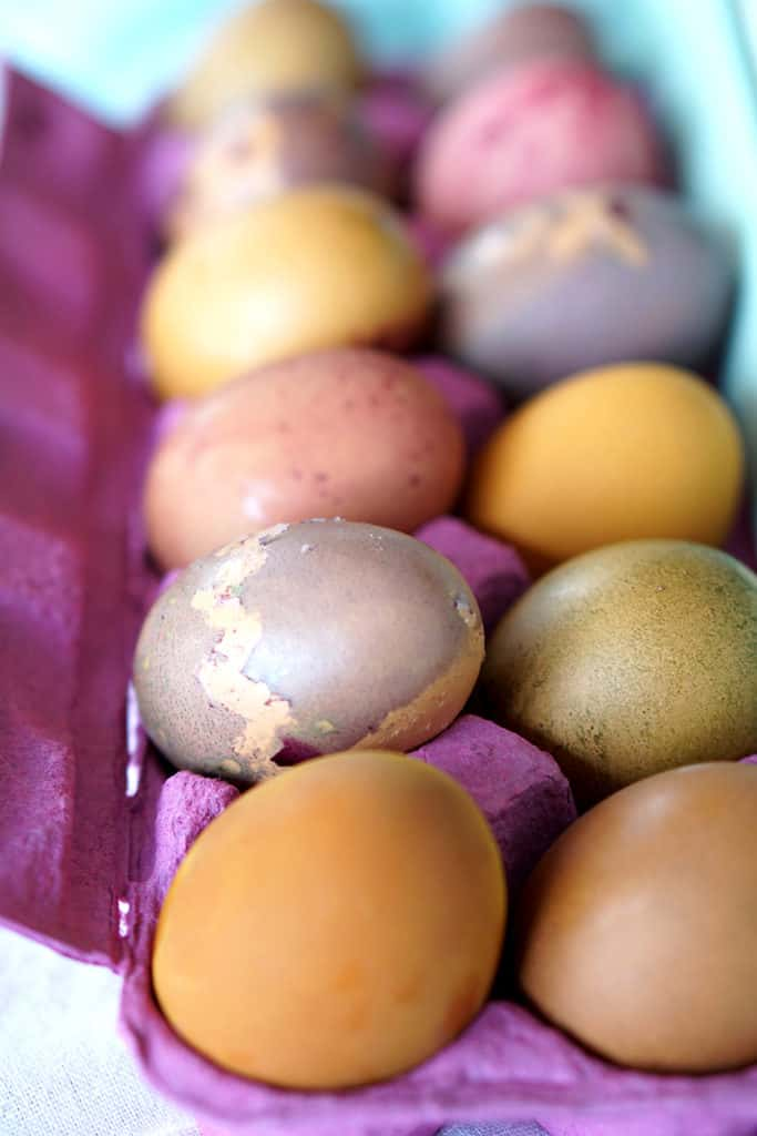 Multi colored eggs for Easter in a pink egg carton