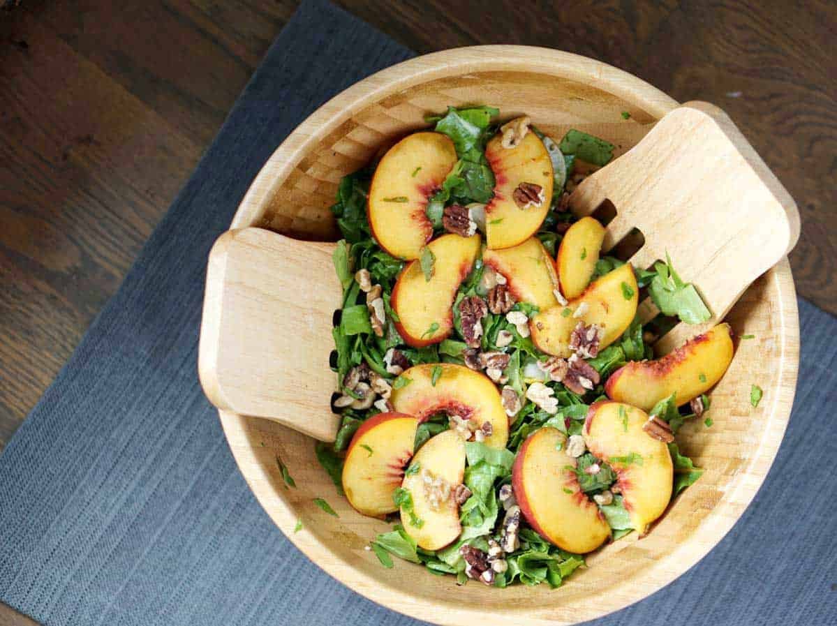 This toasted pecan, cucumber, basil, and peach salad in a large wooden bowl with wooden salad spoons on a darker wooden table is super fresh and incorporates summer and fall flavors into one great gluten and dairy free dish. It's also super quick and sugar-free