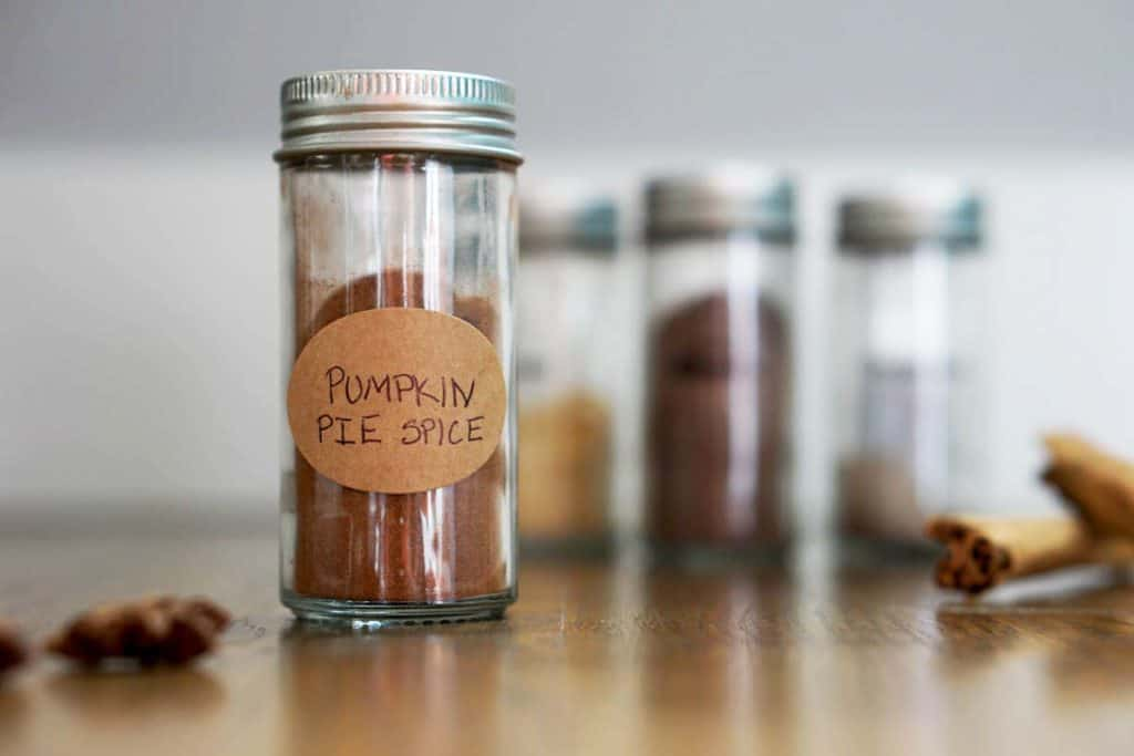 Glass jar of pumpkin pie spice mix on wooden table with other spices around