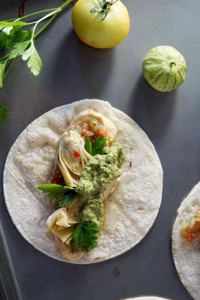 Looking for a healthy meal ready in 5 minutes? Try these Vegan Artichoke Hummus Tacos with Carrot Top Pesto