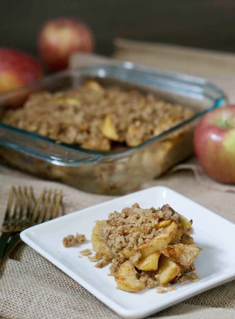 Cinnamon and clove covered apples melting into a paleo, gluten free crumble crust on a white plate next to two bronze forks with fresh apples and a glass tray of apple crisp in the background on burlap canvas tablecloth