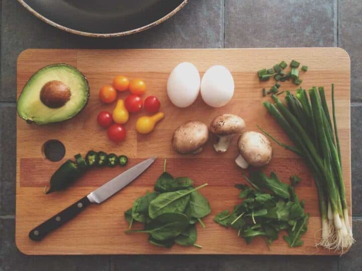 avocado, egg and veggies on a cutting board