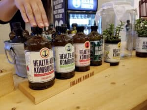 a row of brown glass bottles wit colorful labels for healthade kombucha