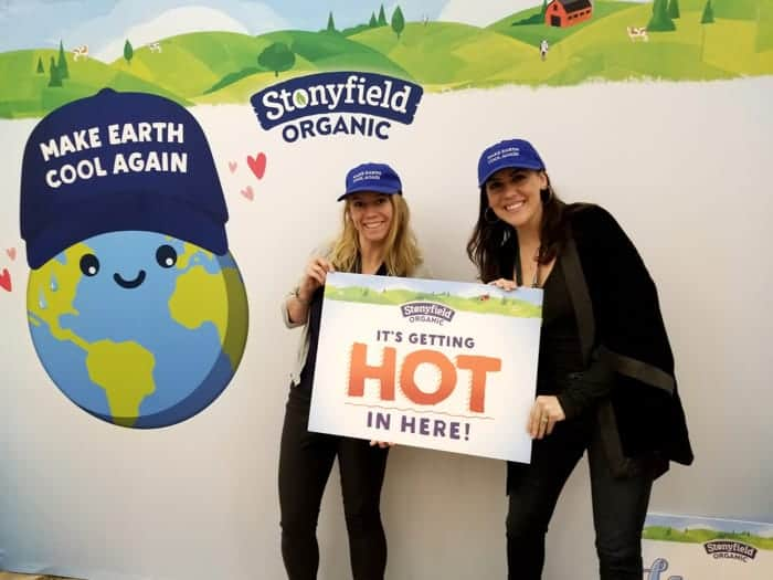 two girls wearing black with a sign saying it's getting hot in here and blue baseball caps saying make earth cool again