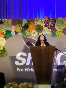Woman at podium in prayer at Shiftcon position