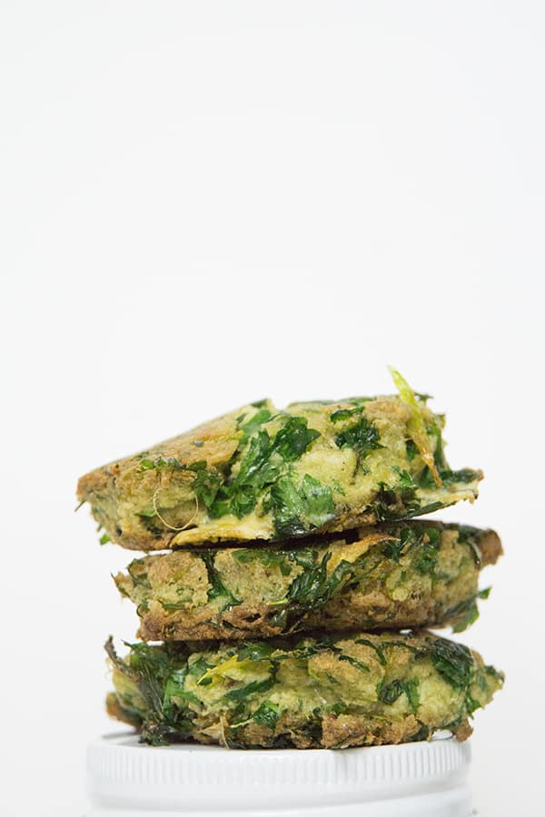 3 celery and parsley fritters stacked on top of each other on white background