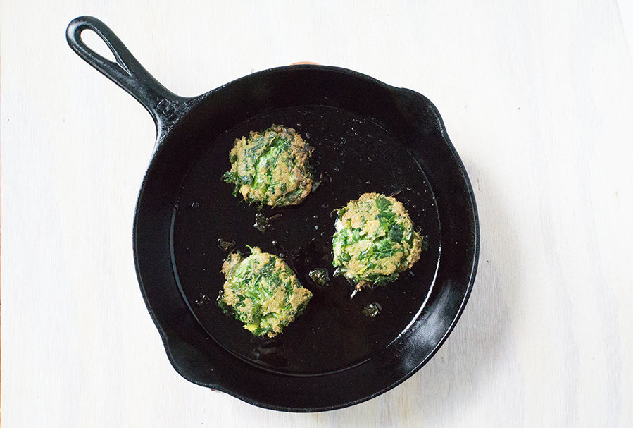 3 celery fritters frying in a cast iron skillet on white wood background