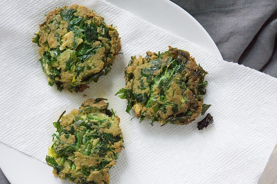 Just fried celery pulp and parsley patties on a white plate
