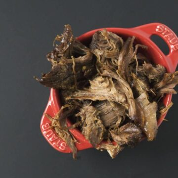 Slow cooked pulled beef in red Staub ramekin on black background