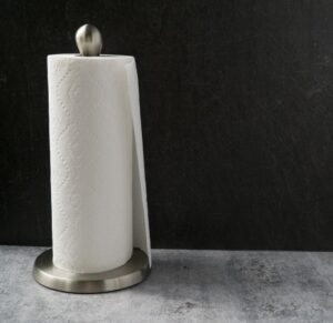 Roll of paper towels on silver paper towel roll on the cement table with black background