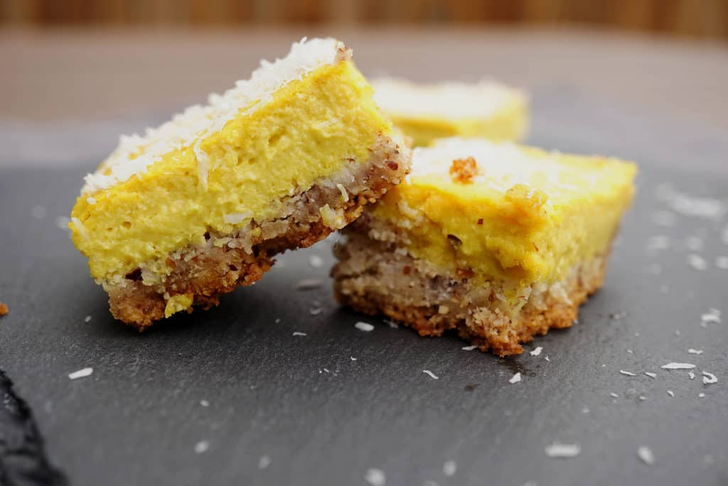 Yellow lemon bars with nutty crust stacked on top of eachother on a black slate tray with a wooden background