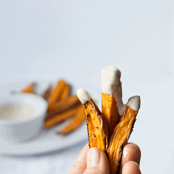 hand holding 3 sweet potato fries dipped in whipped tahini sauce with sauce and fries in the background.