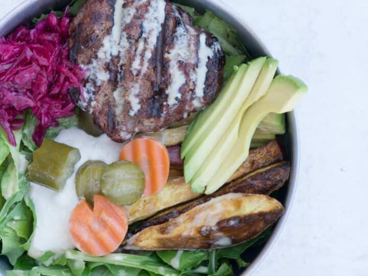 Paleo Elk Burger Bowl in Tin bowl on cement background: mixed greens topped with cashew cream, pickled cucumbers and carrots, roasted sweet potato fries, red sauerkraut, elk burger and tahini