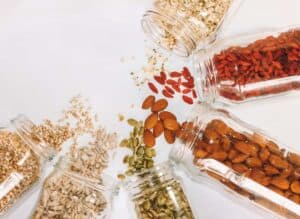 Various seeds from glass mason jars pouring out onto a white counter top