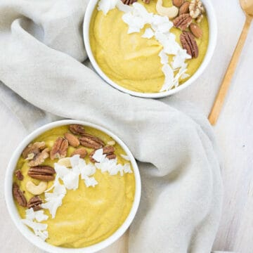 Orange Pumpkin smoothie bowls topped with roasted nuts and coconut flakes, with linen napkins