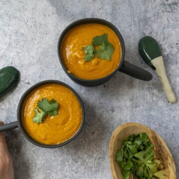 Grabbing a mug of Pumpkin Thai Curry Soup garnished with cilantro
