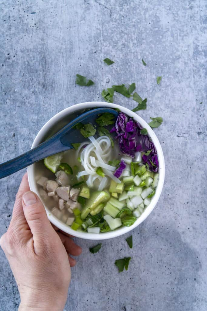 Hand and spoon on Gluten Free Pho Bowl