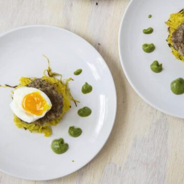 1/2 soft boiled egg over sausage pattie and spaghetti squash next with dotted green sauce on white plates