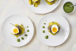 1/2 soft boiled egg over sausage patties and spaghetti squash nests with dotted green sauce on white plates