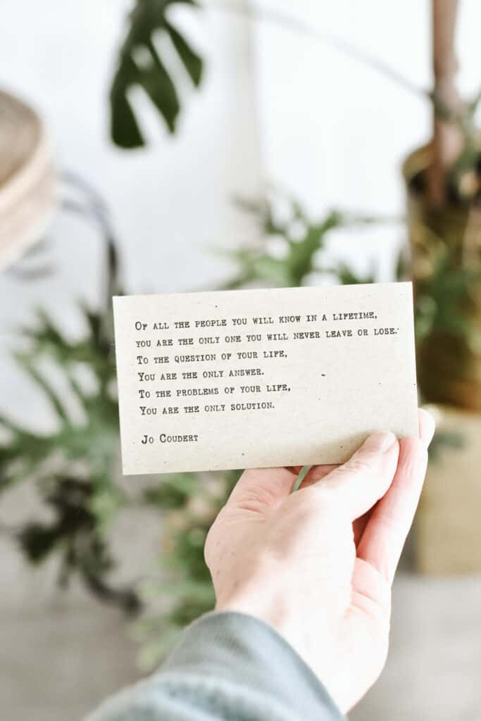 Woman's hand holding a self-love poem in plant filled living room