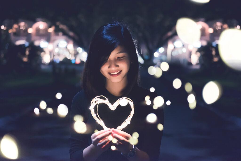girl holding light-up heart in dark street