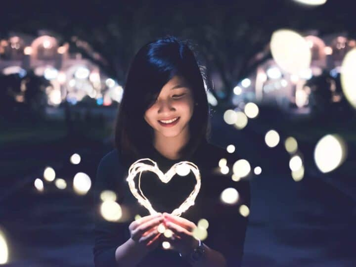 girl holding light-up heart in dark street