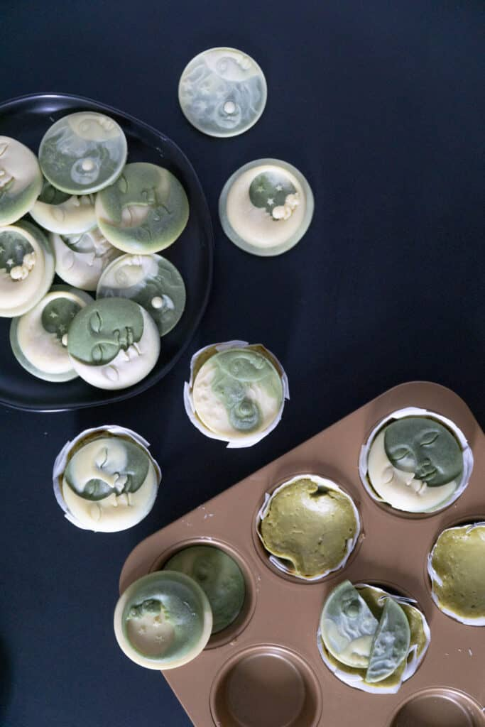 Mini Moringa Cheesecakes with White Chocolate Moons on black with muffin tin