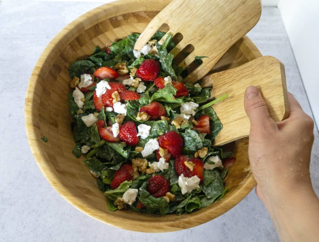 Hand Tossing Strawberry Spinach Salad