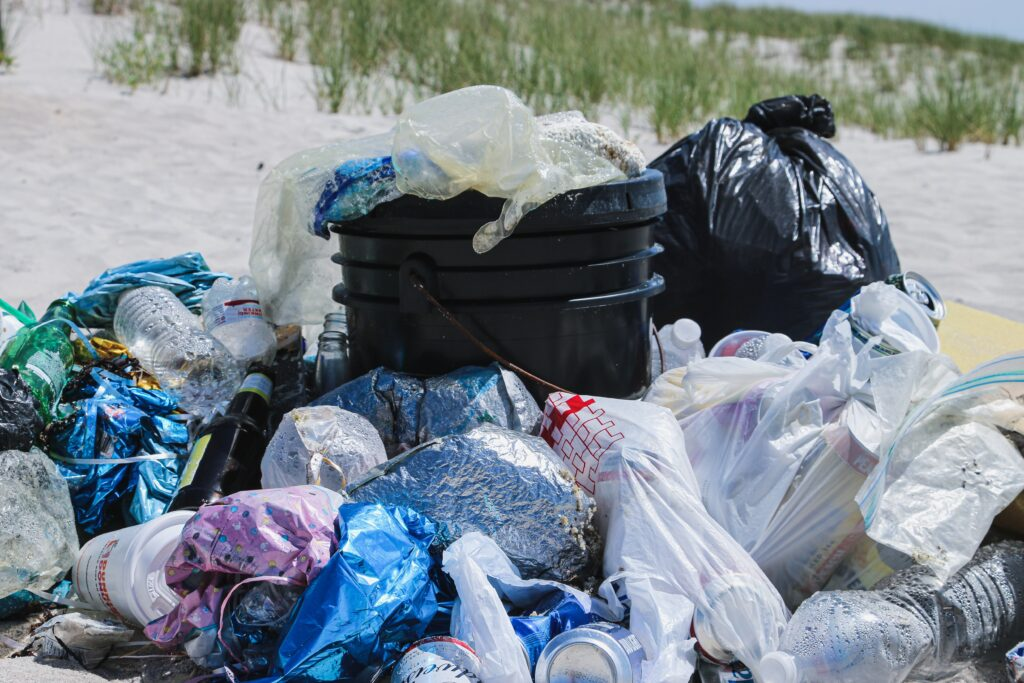 Overflowing plastic bags of trash with plastic spilling out all over the beach