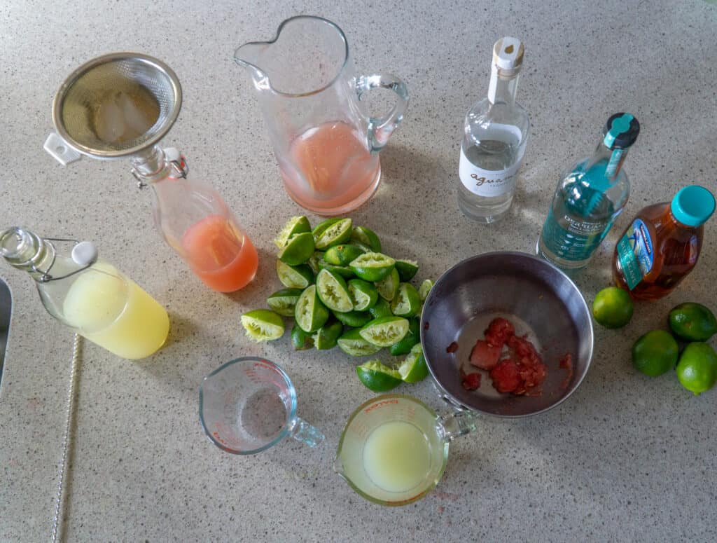 Jars of liquor, batched margaritas and spent limes making batched margaritas