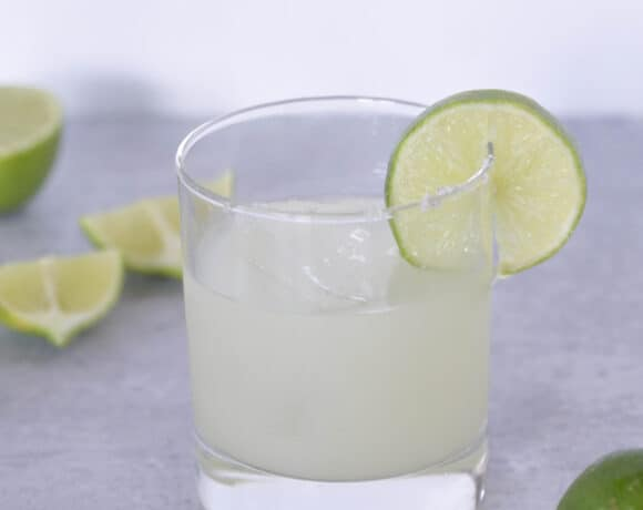 side view of Lime wedge in salted margarita glass with limes