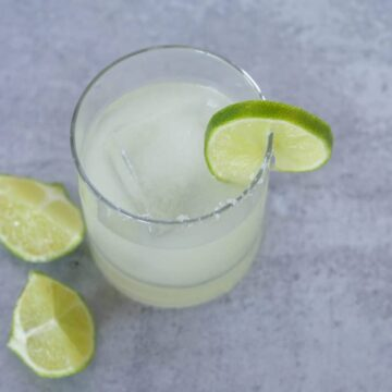 Salt rimmed margarita in glass with limes