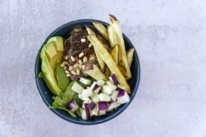 Overhead view of A hand grabs a Fig Tahini Burger bowl with sweet potato fries, kohlrabi and avocado
