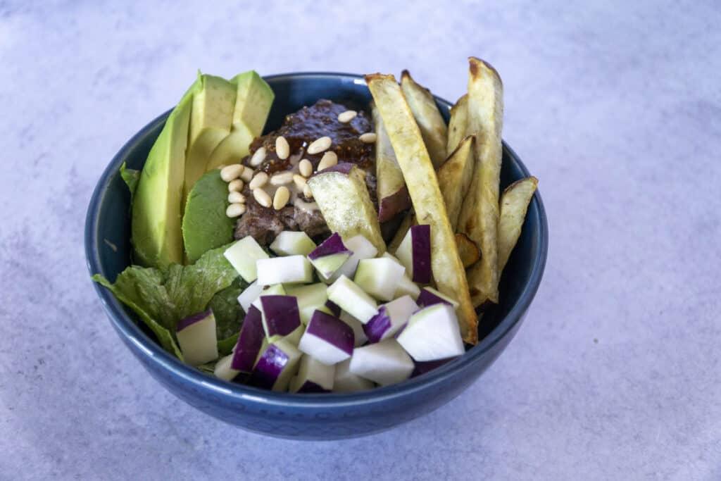 Side view of Fig Tahini Burger bowl with sweet potato fries, kohlrabi and avocado