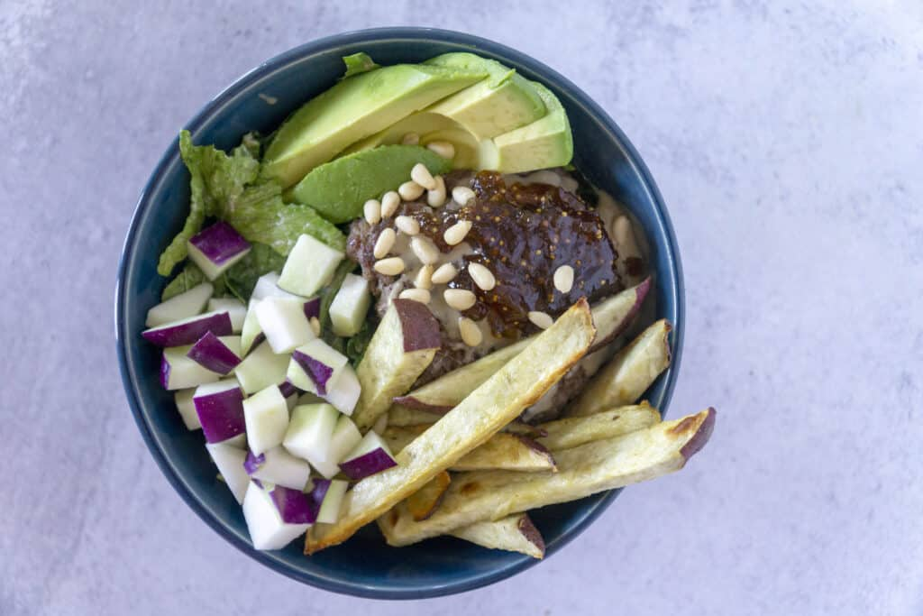 Overhead view of A hand grabs a Fig Tahini Burger bowl with sweet potato fries, kohlrabi and avocado