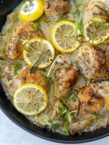 Cast iron skillet of rhubarb chicken with lemon