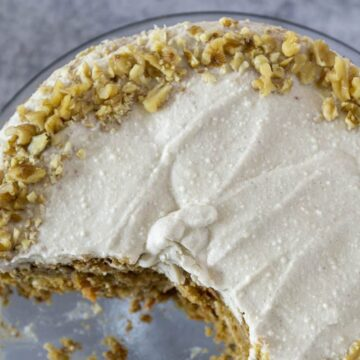 Overhead of ricotta frosted GF carrot cake with crushed walnuts