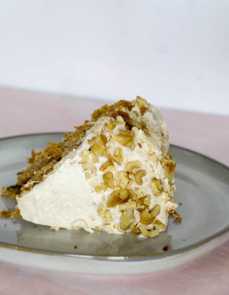 Carrot cake dressed in crushed walnuts sitting on it's side on a pink table