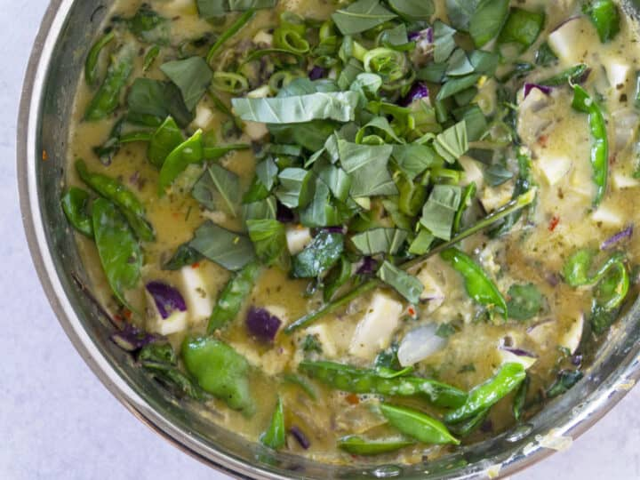 Green curry with snap peas and herbs in copper pot