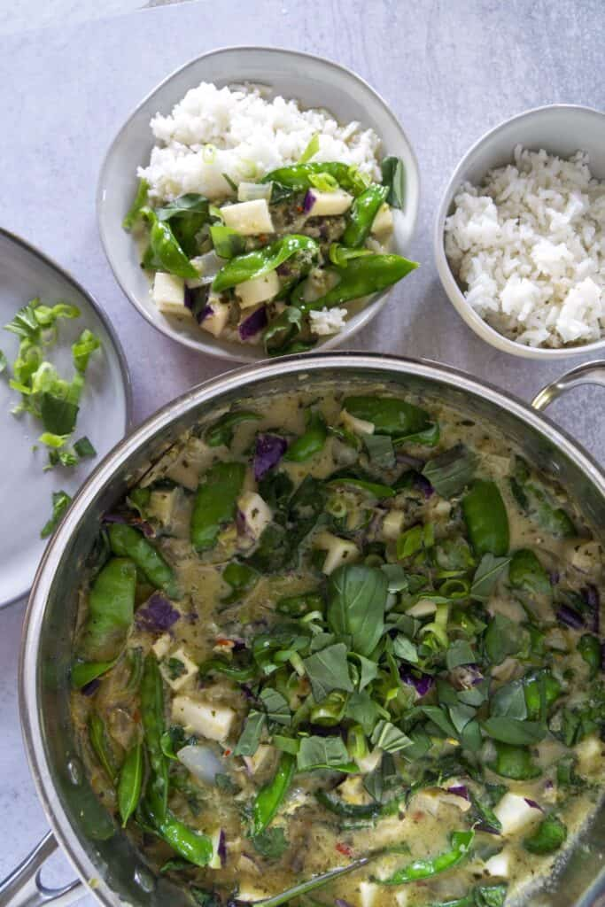 Snap pea and johlrabi curry in a pot with bowl of rice and green onions for garnish