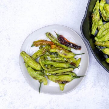 Blistered Shishito peppers on a plate next to a cast iron of peppers